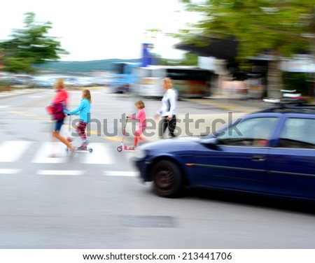 Dangerous city traffic situation with children, parents and car in motion blur