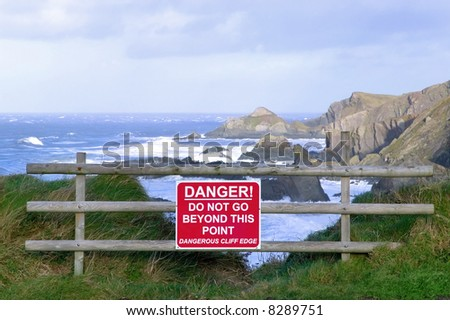 Dangerous cliff edge with warning sign. - stock photo