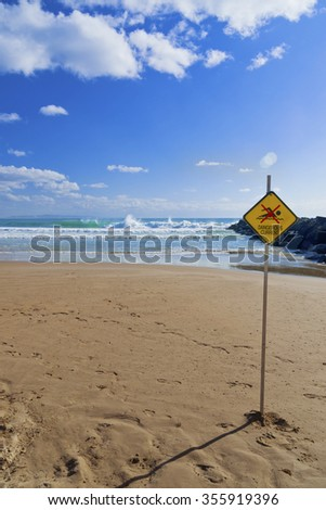 Dangerous current sign on beach. Diamond shaped orange or yellow sign with figure of swimmer crossed out with red. Sign attached to a pole and stuck in the sand on a beach.  - stock photo