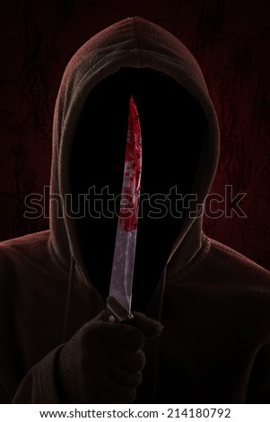 Dangerous hooded man standing in the dark and holding a bloody knife - stock photo
