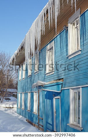 Dangerous icicles hanging from the roof of a wooden house - stock photo
