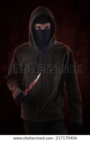 Dangerous killer standing in the dark and holding a bloody knife - stock photo