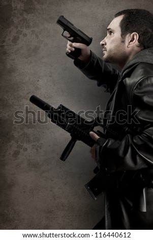 Dangerous man armed with a pistol and machine gun - stock photo