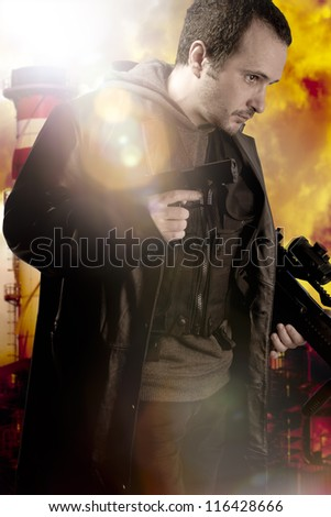 Dangerous man armed with a pistol, thief over factory background - stock photo