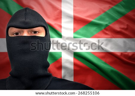 dangerous man in a mask on a basque flag background - stock photo