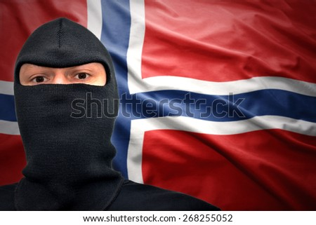 dangerous man in a mask on a norwegian flag background - stock photo