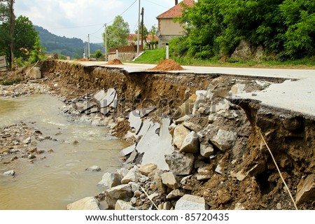 Dangerous part of landslip road section after flooding - stock photo