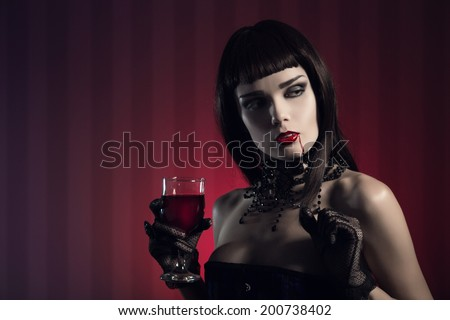 Dangerous sexy vampire girl in glamorous outfit with glass of wine or blood  - stock photo