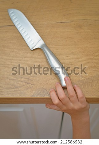 Dangerous situation in the kitchen. Child is trying to get a kitchen knife. - stock photo