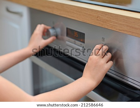 Dangerous situation in the kitchen. Child playing with electric oven. - stock photo