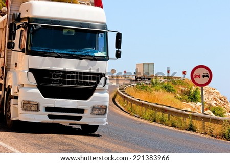dangerous turns and loaded trucks in the mountains - stock photo