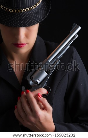 Dangerous woman in black with silver handgun and stylish hat - stock photo