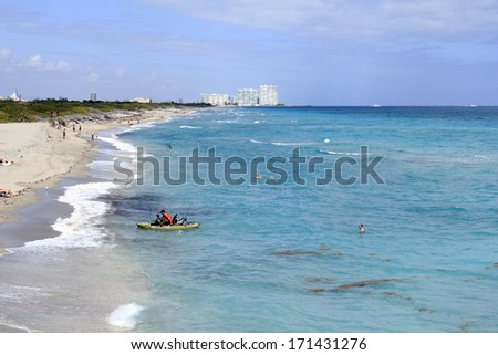 DANIA BEACH, FLORIDA - FEBRUARY 20, 2013: Long distance view of the sunny and tropical blue water shoreline with people, foliage, boats and buildings in the background seen from above the water.  - stock photo