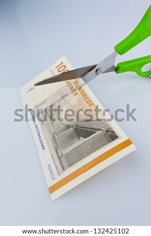 danish crowns. currency from denmark in europe and scissors. duties and taxes. - stock photo