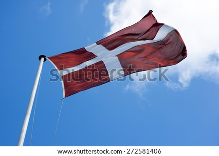 Danish flag in strong winds sky blue. - stock photo