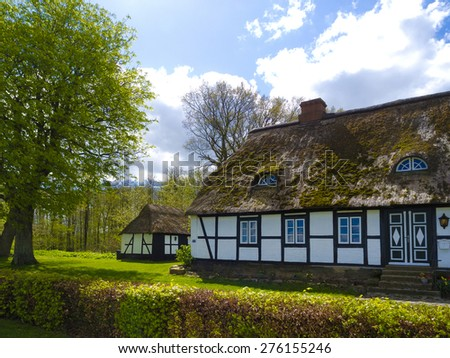 danish style countryside cottage with thatched roof in northern-germany - stock photo
