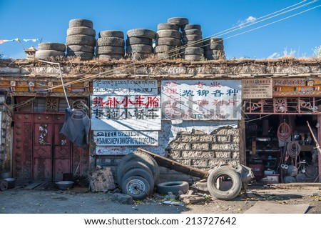 Daocheng, Sichuan ,China - October 23,2008 : Scene of tire shop service in Daocheng, Sichuan Province, China.Daocheng  is a county of western Sichuan located at an altitude of 3750m. - stock photo