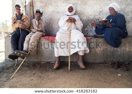DARAW, EGYPT - FEBRUARY 6, 2016: Group of local camel salesmen resting on the wall. - stock photo