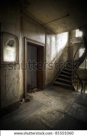 Dare to go up the stairs? A creepy hallway in a moody atmosphere. - stock photo