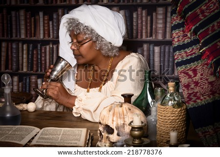 Dark alchemist tasting a brew from her laboratory - stock photo