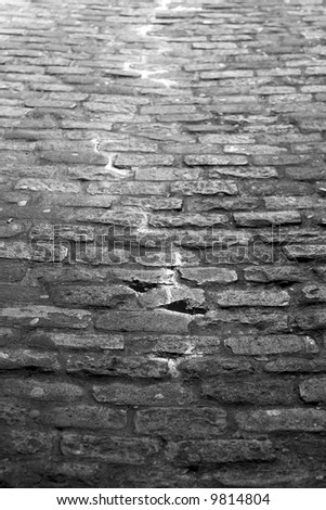 dark alley with cobblestones and water running down the middle in black and white - stock photo