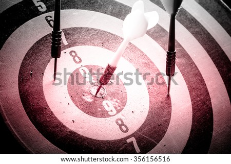 Dark and red tone - Dart is an opportunity and Dartboard is the target and goal with vintage retro picture style. success/fail business concept. Bullseye and Dart. - stock photo