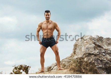 Dark and ripped. Fit attractive shirtless man posing outdoors looking to the camera. - stock photo