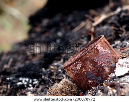 dark ash and rest of burned toxic waste such as plastic metal and daily used chemical as human-made surrounding pollution environment leaving on the ground and water in nature for the next generation  - stock photo