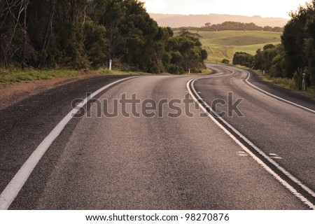 Dark asphalt road with bright white lines curves downhill with trees on sides and green farm fields and horses in far away in bright sunrise in Victoria, Australia - stock photo