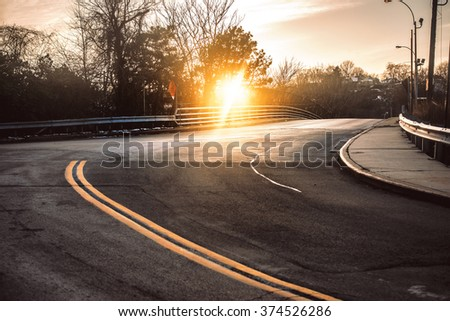 Dark asphalt road with bright yellow lines curves under sunset in small town - stock photo