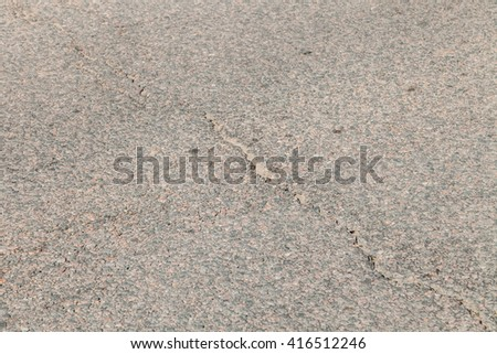 Dark asphalt texture with crack. Damaged pavement - stock photo