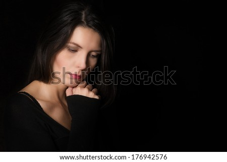 Dark atmospheric portrait of a serene beautiful introspective woman with downcast eyes and a pensive expression in a deep reverie