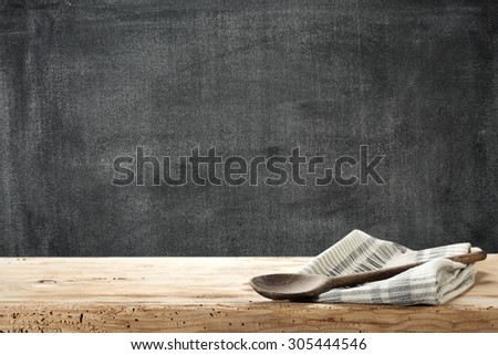 dark background of black board and wooden spoon and napkin  - stock photo
