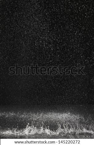 Dark background shot of rain falling - stock photo