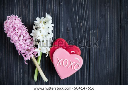 Dark background with fresh flowers hyacinths and biscuits in the