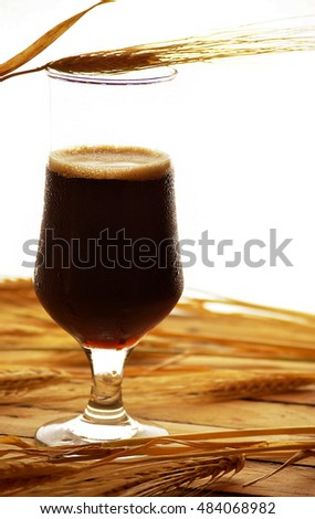 dark beer on the background ears of barley in a glass
