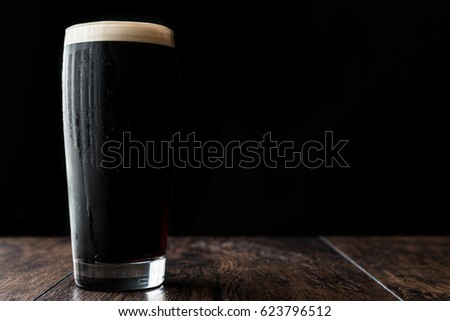 Dark beer on wooden surface. copy space.