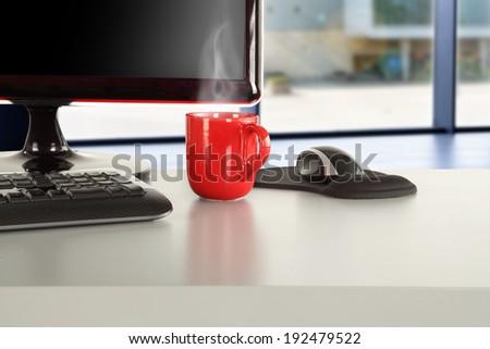 dark black computer and red mug  - stock photo