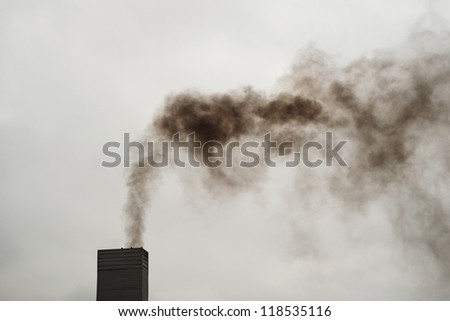 Dark black smoke from the chimney on a cold, cloudy day. - stock photo