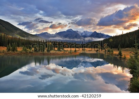 Dark blue cold lake, forest coast and snow mountains in Canada - stock photo