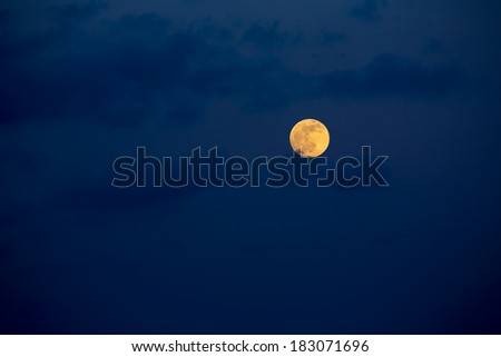 Dark blue sky with full moon and mistery clouds - stock photo