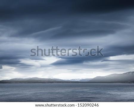 Dark blue stormy clouds over the coastal rocks. Empty Norwegian sea landscape - stock photo