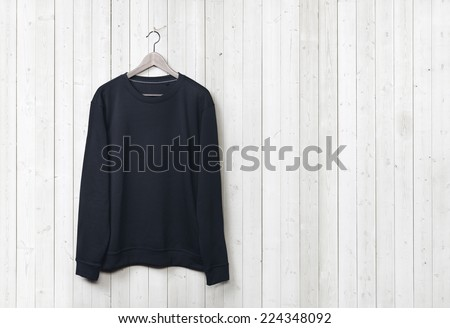 Dark blue sweater on a white wood wall - stock photo