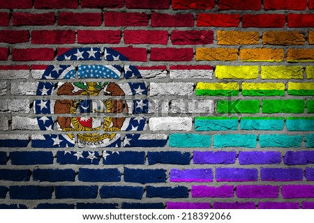 Dark brick wall texture - country flag and rainbow flag painted on wall - Missouri - stock photo
