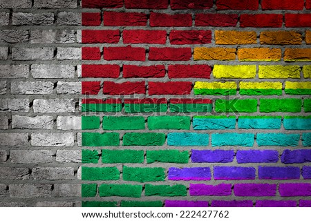 Dark brick wall texture - coutry flag and rainbow flag painted on wall - Madagascar - stock photo