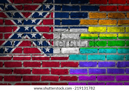 Dark brick wall texture - coutry flag and rainbow flag painted on wall - Mississippi - stock photo