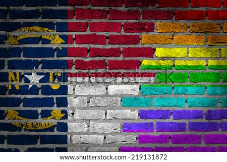Dark brick wall texture - coutry flag and rainbow flag painted on wall - North Carolina - stock photo