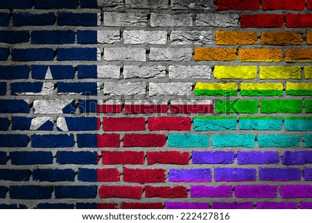 Dark brick wall texture - coutry flag and rainbow flag painted on wall - Texas - stock photo