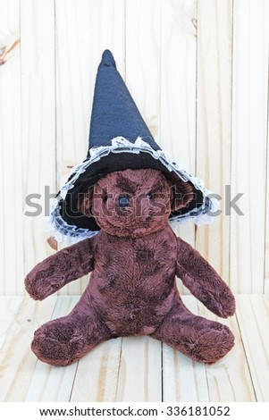 dark brown bear,wears white lace edge and black witch hat,on wood background - stock photo
