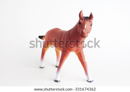 Dark brown horse toy standing on white background and angle view.